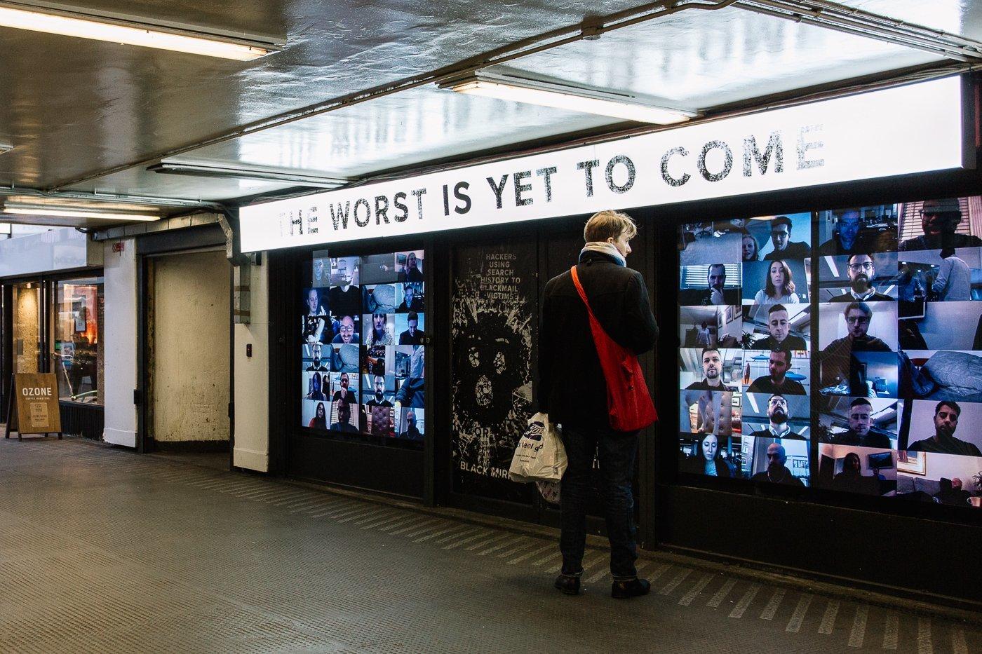 """Pop-up Netflix - Black Mirror à Old Street Station, Londres. Un homme dans le métro se tient devant un panneau """"The Worst is yet to come"""" et regarde des visages sur des écrans."""