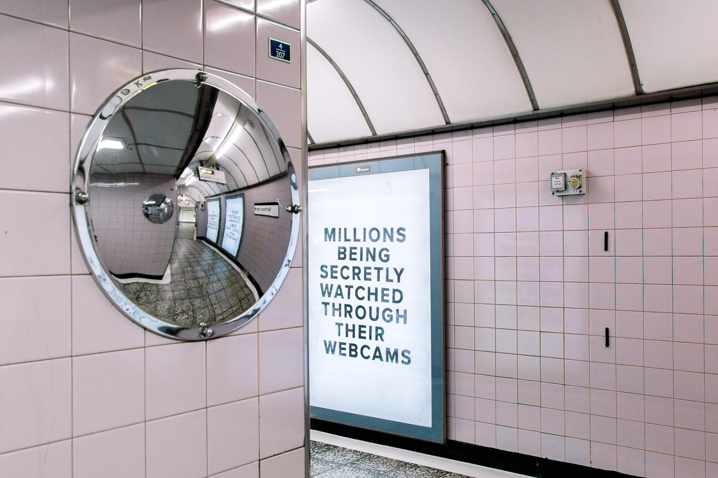 "Pop-up Netflix - Black Mirror à Old Street Station, Londres. Un miroir rond dans un couloir devant un panneau ""Millions being secretly watched through their webcam"""
