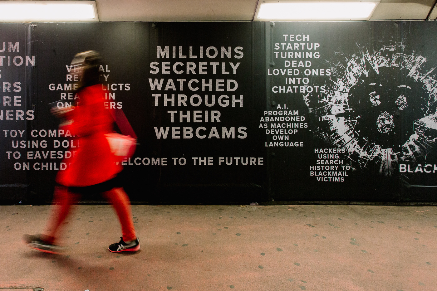 "Pop-up Netflix - Black Mirror à Old Street Station, Londres. Une silhouette rouge flou passe devant un panneau à messages notamment ""Millions being secretly watched through their webcam"""